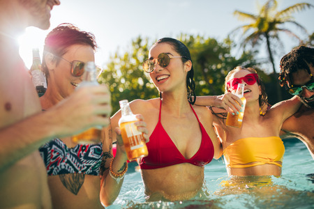 Cheerful group of friends having great time at pool party. Group of men and women enjoying together in the swimming pool with drinks. Stockfoto