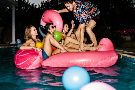 Cheerful men and women in pool on inflatable float. Group of happy friends partying in a swimming pool during evening.