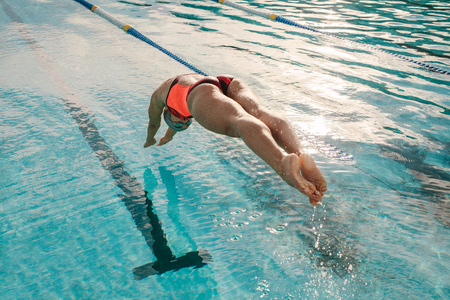 Female swimmer diving into indoor sports swimming pool. Sporty woman practising for competition. Stockfoto