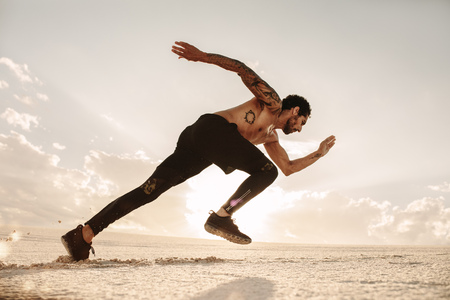 Young male athlete launching off for a run on desert sand. Runner running on sand dune.