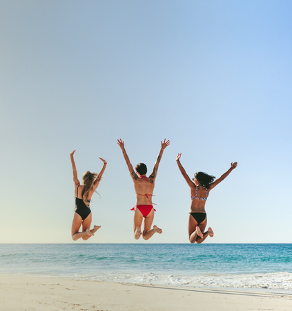Rear view of three women in bikini jumping in air with hands raised and having fun on the beach. Women on vacation enjoying at beach jumping in air facing the sea.