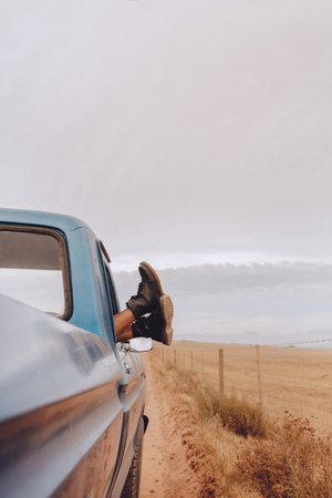 Shot of woman relaxing in a car on road trip. Female feet hanging out of vehicle window.