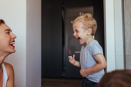 Young woman laughing while a little boy putting on makeup on her face. Small boy doing makeup to his mom and laughing. Mother and son having fun with makeup. 스톡 콘텐츠