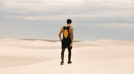Rear view of fit young man with hydration pack walking over sand dunes. Male athlete walking in desert.