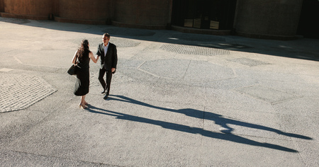Business people greeting each other and shaking hands on a street while commuting to office. Businesswoman shaking hand with a colleague outdoors with their long shadows on the ground.