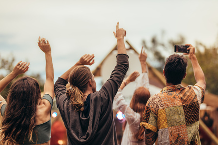 Rear view of young people at music concert. Group of men and woman raising hands and taking pictures at music festival.