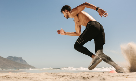 Man doing fitness workout at a beach on a sunny day. Side view of an athletic man setting off for a sprint on the beach.