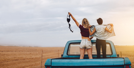 Rear view of two woman standing in the back of a open truck while traveling to country side. Woman holding her bra with friends standing with unbuttoned shirt. Stock Photo
