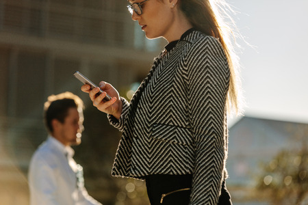 Woman looking at her mobile phone while walking on street to office. Busy office going woman walking on street and using her mobile phone with sun flare in the background. Stock Photo
