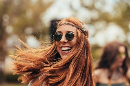 Mujer caucásica en look retro disfrutando en el festival de música. Hermosa mujer joven sonriendo con gafas de sol en el parque. Foto de archivo