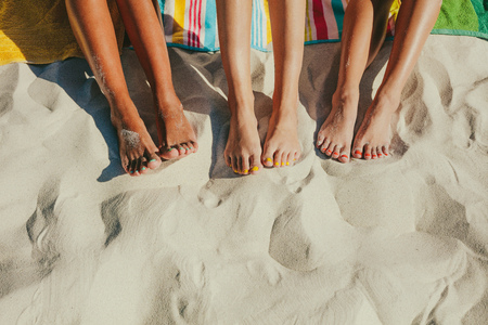 Close up shot of legs of three women sitting on the beach with nails painted in different colours.