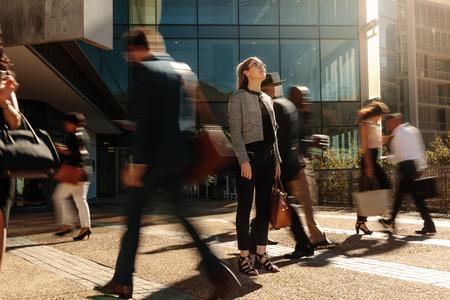 Donna in piedi in mezzo a un ufficio affollato che va folla agganciata ai loro telefoni cellulari. Imprenditrice tenendo la sua borsa a mano in piedi ancora su una strada trafficata con persone che passano davanti a lei utilizzando i telefoni cellulari.