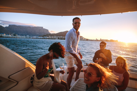 Happy friends drinking and having fun in boat party. Young rich people enjoying sunset boat party.