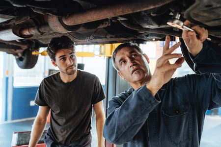 Mature male mechanic discussing and showing something under the car to coworker. Mechanic and male trainee working underneath car together