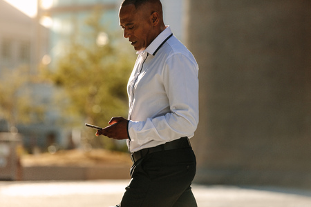 Man in formal clothes looking at his mobile phone while walking on street. Busy office going person walking on street and using his cellphone.