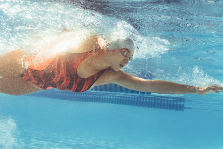 Underwater shot of young woman swimming in pool. Female swimmer inside swimming pool. Stock Photo