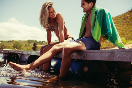 Smiling young couple sitting on the pier dangling legs in water. Young man and woman relaxing on a jetty at the lake. Both in swimwear. Stock Photo - 107116420