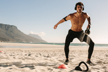 Man doing fitness workout at a beach using a kettlebell. Bare chested athletic man doing exercise with kettlebells wearing wireless headphones and mobile phone fixed to armband.