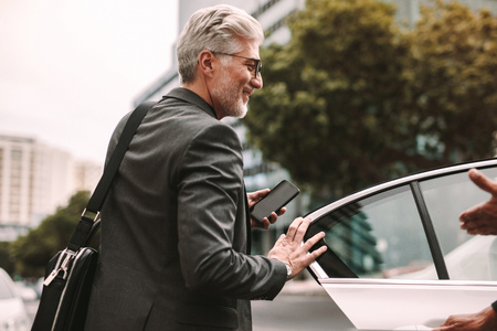 Happy mature commuter getting into a taxi. Businessman entering a taxi with driver opening door.