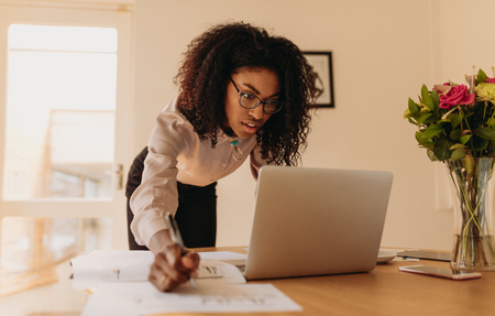 Businesswoman making notes looking at a laptop computer at home. Woman entrepreneur leaning over the table to write notes while looking at the laptop. Stock Photo