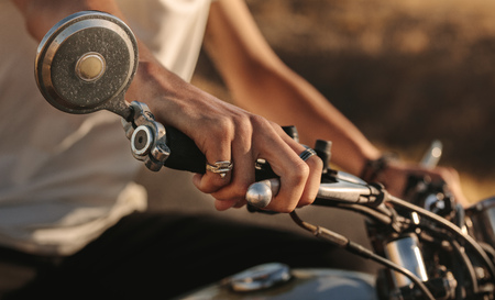 Close up of man holding the handlebars with the front brake lever. Male riders hand on the handlebar of motorcycle. Imagens