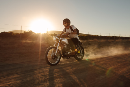 Young man riding a vintage motorcycle off-road. Rider driving a bike very fast on countryside road.