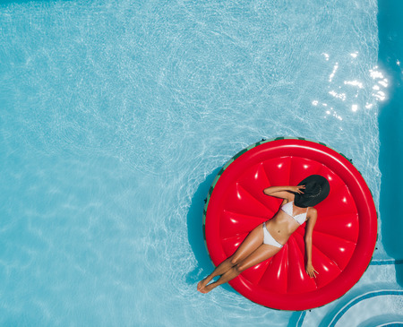 Top view of woman in bikini relaxing on floating mattress in the pool water in hot sunny day. Female sunbathing in swimming pool with hat on her face. 版權商用圖片 - 113590975
