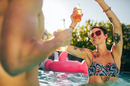 在泳池派对上,穿着比基尼跳舞的漂亮年轻人手里拿着啤酒。在夏日与朋友聚会的女性。