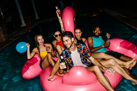 Group of men and women having beers on an inflatable pool float mattress in evening. Friends hanging out together in a pool party. 版權商用圖片