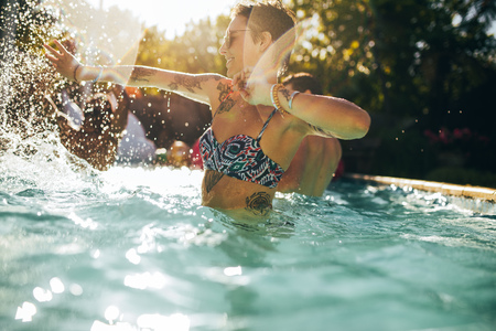 Woman in bikini having fun with friends in swimming pool. Friends playing and splashing water on each other in pool. Stockfoto