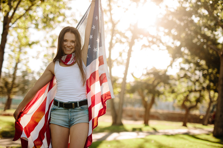 Portrait of a beautiful woman in the park with American flag. Smiling american girl holding national flag proudly and looking at camera.