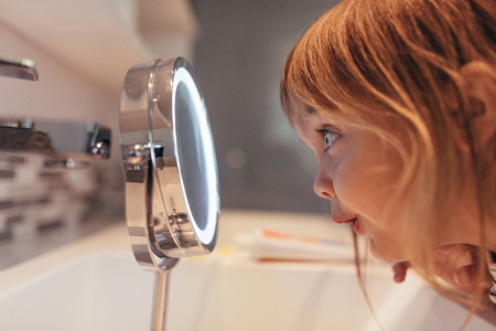 Close up of a little girl looking at a small mirror in bathroom. Side view of a girl looking at a mirror in awe. Stok Fotoğraf
