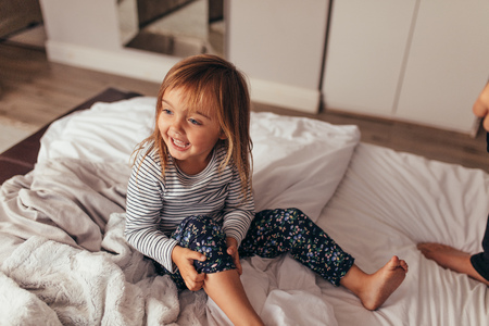 Little girl sitting on bed playing with her father. Happy girl playing on bed at home.