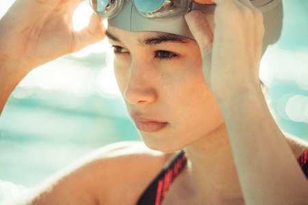 Female swimming athlete adjusting her goggles at the pool. Woman swimmer preparing for a swimming training. Stock Photo - 107131681