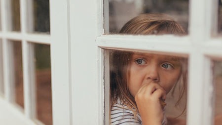 Close up of a little girl sitting beside a window and looking outside. Grey eyed girl eating a cake while looking out of a window.