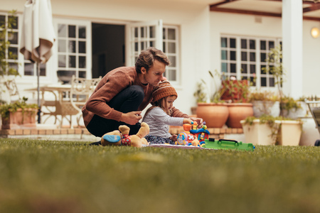 Father and daughter sitting in the garden and playing with toys. Father and daughter spending time together sitting in their backyard. Imagens - 107131743