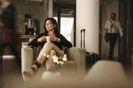 Empresaria sentada en el salón del aeropuerto, esperando el vuelo. Mujer pensativa sentada en el sofá con café en la zona de espera del aeropuerto. Foto de archivo