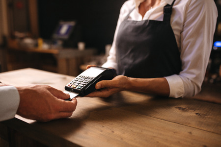 Female bartender holding a credit card reader machine with male customer inserting the card in machine for payment.