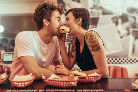 Happy couple at a restaurant eating a burger together looking at each other. Man and woman sitting in a diner with food on the table sharing a burger. Archivio Fotografico