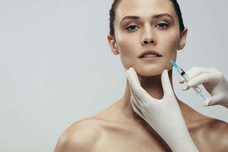 Portrait of young woman getting cosmetic injection. Close up of beautiful woman gets injection in her face against grey background with copy space. Banco de Imagens
