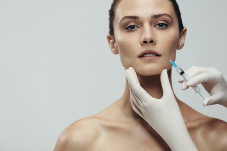 Ritratto di giovane donna che ottiene iniezione cosmetica. Primo piano di bella donna ottiene iniezione in faccia contro uno sfondo grigio con spazio di copia. Archivio Fotografico