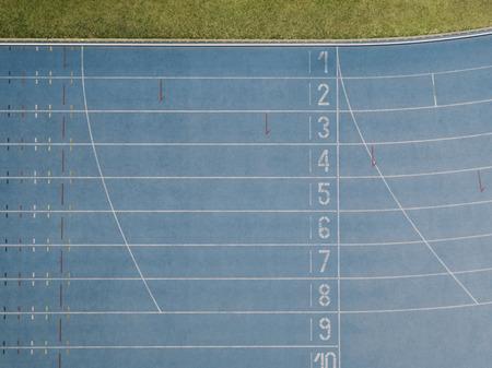 Vista aérea de la línea de meta de una pista de atletismo. Vista superior de la pista de atletismo azul para todo clima en un estadio.
