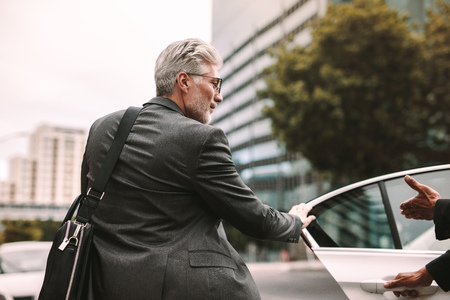 Mature businessman getting into a cab with driver opening door. Businessman entering a taxi on city street. Banco de Imagens - 107260294