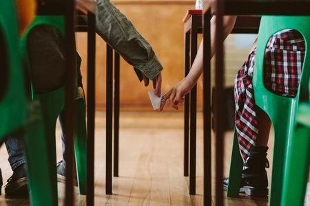 Dos estudiantes se pasan notas entre sí en secreto durante la clase. Jóvenes estudiantes haciendo trampa en un examen. Foto de archivo