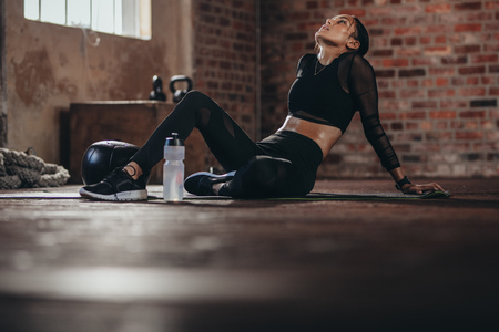 Tired woman having rest after workout. Tired and exhausted female athlete sitting on floor at gym with a water bottle.