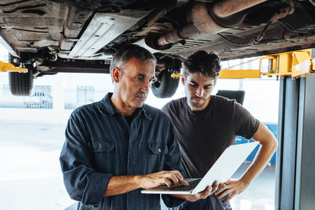 Auto service professionals using a laptop while examining the car. Banque d'images