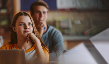 Pretty teenage student paying attention to lecture in classroom. Woman studying at the college classroom. Banco de Imagens