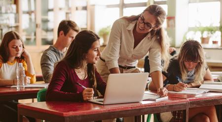 Uśmiechnięta kobieta wykładowca pomaga studentowi podczas jej zajęć. Student na wykładzie z pomocnym nauczycielem.
