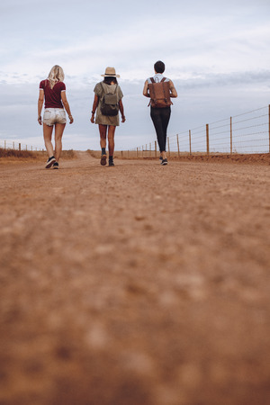 Vertical shot of three women friends together walking down the country road leaving their car behind. Female friends walking on a rural road after their car breakdown. Stock Photo