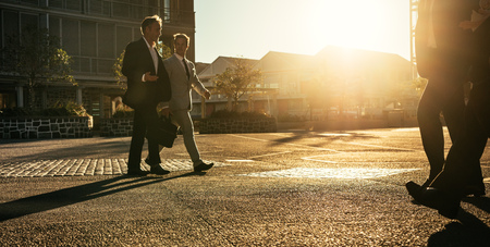 Men in formal clothes commuting to office early in the morning carrying office bags. Business colleagues talking while walking on city street with sun flare in the background.